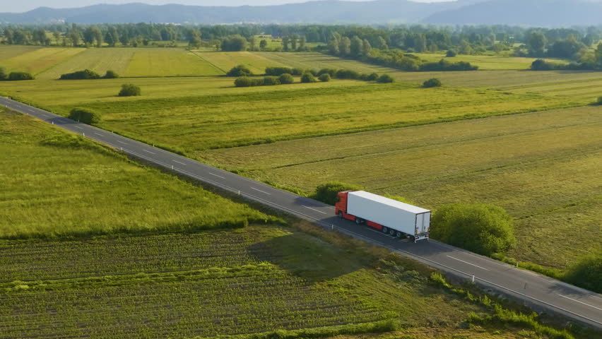 Aerial shot of a fast truck on the road in beautiful countryside with green grass in the summer.