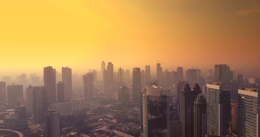 Beautiful aerial view of skyscrapers tower in Jakarta city with orange sky at dusk time, shot in 4k resolution