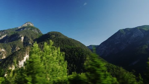 Beautiful Alps in Austria. Covered with forests, clouds can be seen above the peaks. View from the window of a moving car, pov video