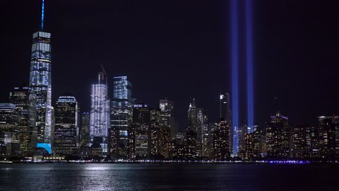 Two beams of light rise up into the New York City skyline at night, as aircraft fly by and boats travel across the Hudson River.