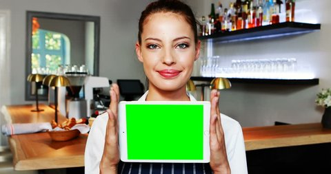 Portrait of beautiful waitress holding digital tablet at counter in resturant