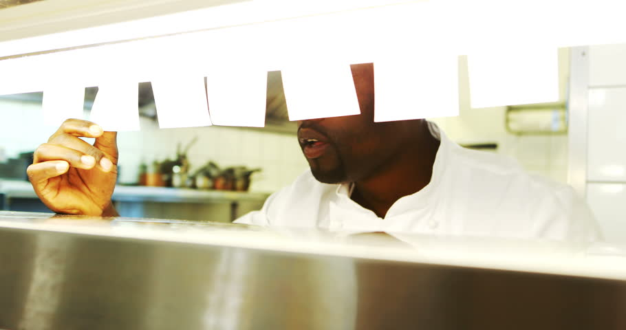 Chef looking at order list while serving food at order station in resturant
