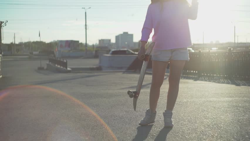 Portrait of a hipster young girl smiling with a skateboard at sunset. Slow motion #29335567
