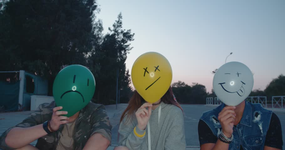 Hipster teenage friends celebrating holding emoticon balloons and making funny faces in city streets