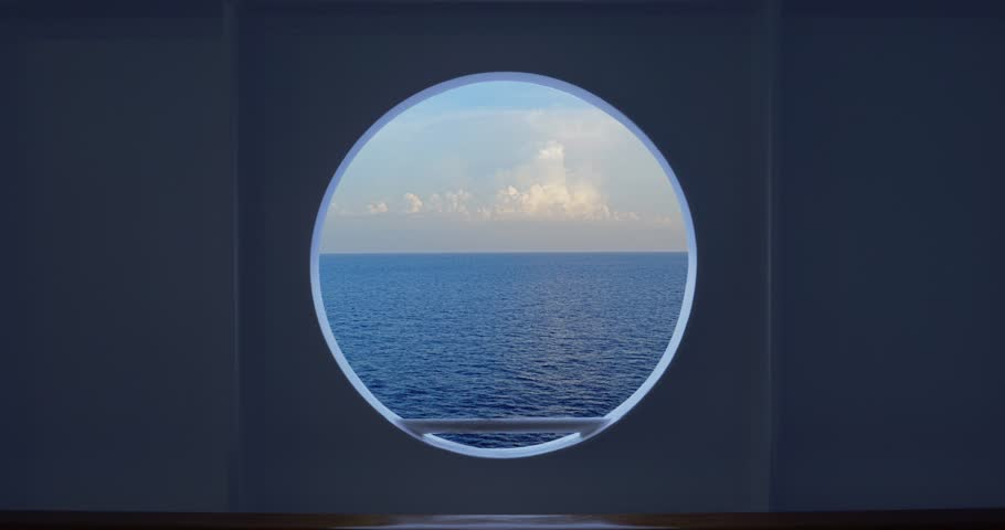 Static shot looking out at the open ocean and horizon from a cruise ship's porthole.