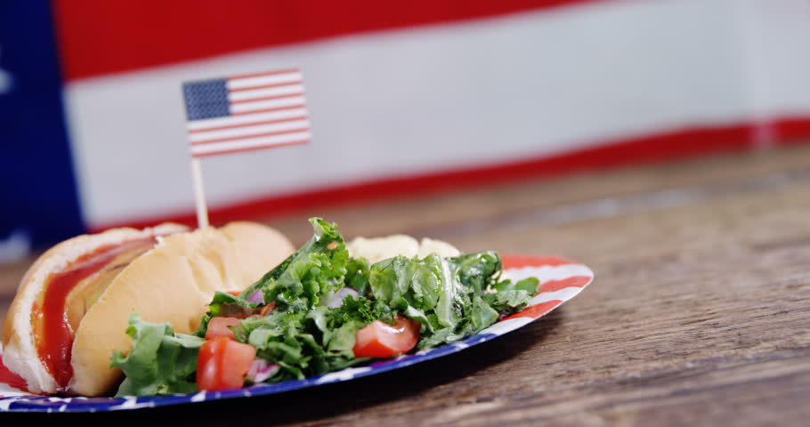 Close-up of hot dog french fries and hamburger served on plate against American flag