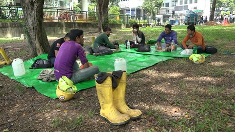 SINGAPORE - MAY 2017: Indian migrant workers enjoy lunch in public park near construction site in Singapore