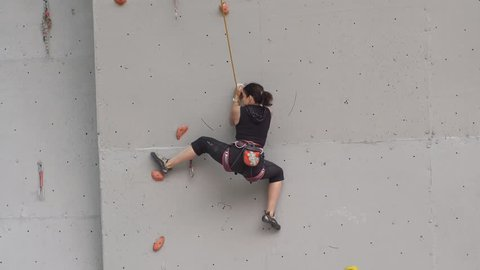 young woman exercising at indoor climbing gym wall. training climbers on the climbing wall. girl has workout of rock-climbing in sport gym.