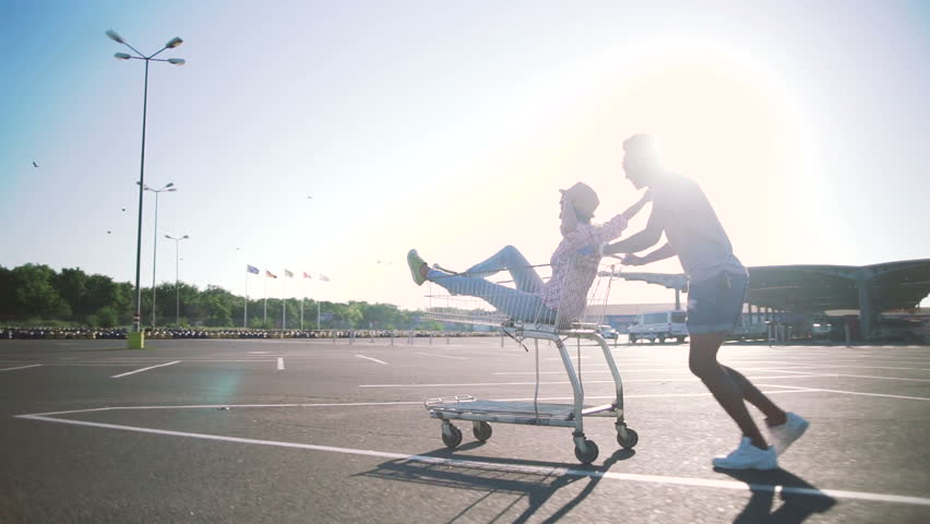 Young friends having fun on shopping trolleys. Multiethnic young people racing on shopping cart. slow motion | Shutterstock HD Video #29413315