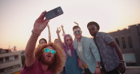 Multi-ethnnic hipster friends partying with champagne and taking selfies at rooftop summer party