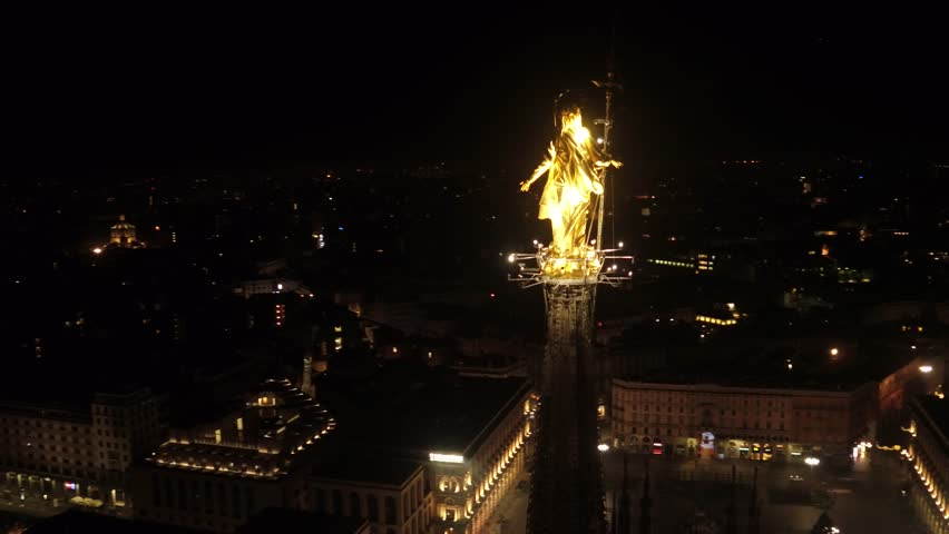 Aerial drone footage View of famous statue of cathedral Duomo/Dome in Milan/Milano Italy by night // no video editing