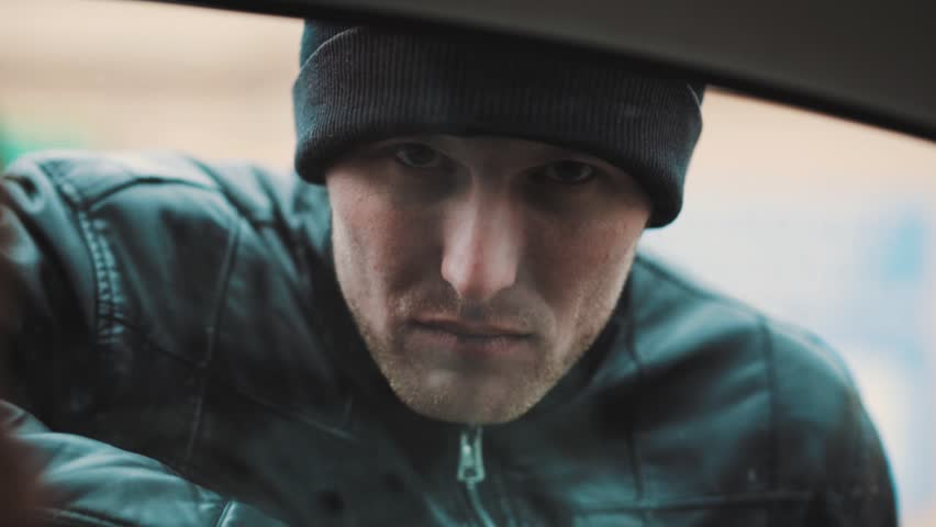 Unshaved caucasian man in black leather jacket and beanie hat heavy look into camera trough car window glass