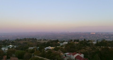 An aerial shot flying over Northcliff Hill toward Johannesburg's central business district on the horizon; Hillbrow Tower on the left and Sentech Tower on the right.