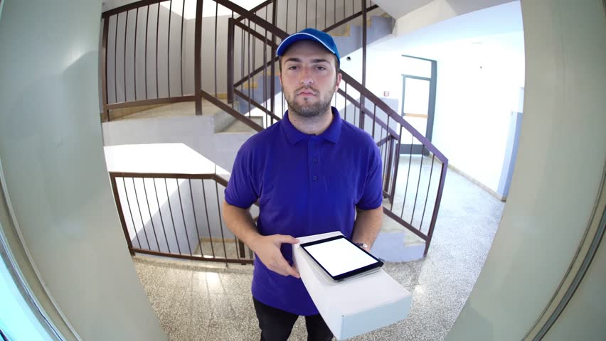 Courier in a blue uniform holding a parcel making a home delivery as seen through a spyhole. Shot with a fisheye lens.