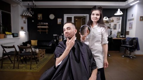 Happy handsome man in barbershop looking at himself in big mirror after hairstyling. Female barber is demonstrating to client the result of hairstyling. Pleased smiling man expressing happiness.