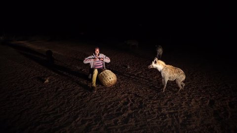 A man taking a phone call in the middle of feeding wild hyenas in Harar, Ethiopia/Phone Call during Hyena Feeding