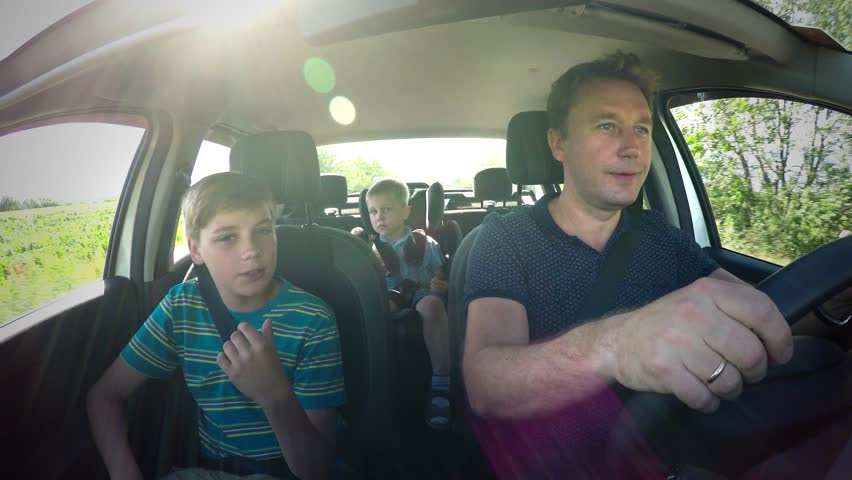 Children boys brothers travel in the car with parent father in vehicle interior with seat belts, teen and cute baby caucasian kid boy in a child car seat. Safety of movement in motor transport