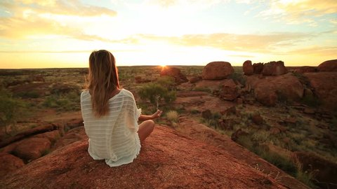 Caucasian female meditating at sunrise Young woman at the devil's Marbles sitting on a boulder exercises yoga at sunrise. Devils Marbles Conservation Reserve, Northern Territory, Australia.