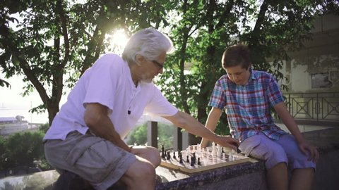 Grandfather and grandson are playing chess in park