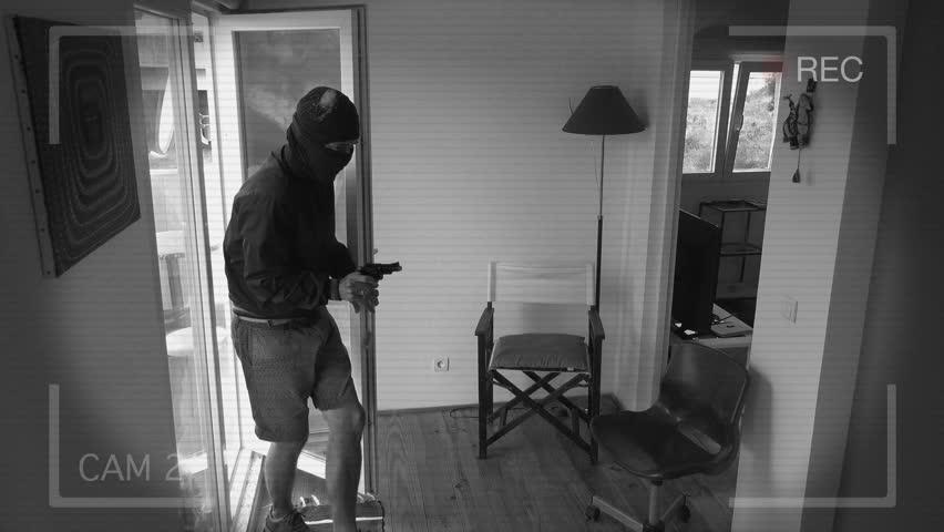 CCTV Camera Records A Home Burglary. Burglar with a gun breaks Into a house filmed on home security camera