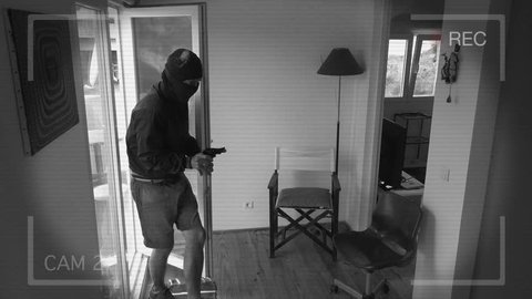 CCTV Camera Records A Home Burglary. Burglar with a gun breaks Into a house filmed on home security camera