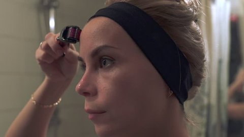 Young woman using a derma roller for micro needling therapy face. Mesoroller for micro facial massage. Roller, microneedle, mesotherapy, rejuvenating, beautification, skin care at home