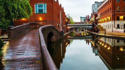 Birmingham, UK. People walking during the rain in the evening at famous Birmingham canal in UK. Time-lapse with motion blurred people