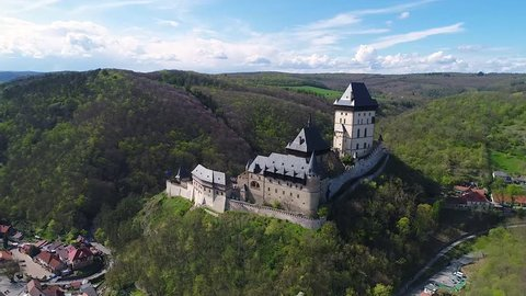 Aerial video of royal castle Karlstejn medieval castle near Prague in spring nature, lit by evening sun. Romantic Czech castle on the hilltop against dramatic blue sky. Central Bohemia, Czechia.