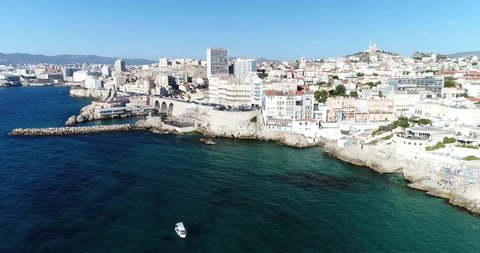 Aerial : Flying over Marseille  beautiful coastline . Cityscape panorama with edifice of Notre Dame de la Garde and Old port at summer sunny day.  France