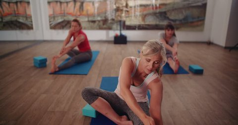 Beautiful active elderly woman exercising and stretching her arms and legs during yoga class