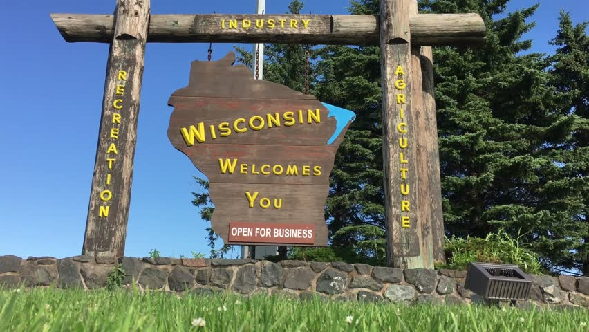 Welcome to Wisconsin sign in sunlight; shot from ground with blue sky backdrop.