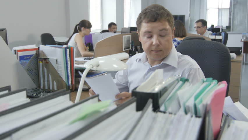 KAZAN, TATARSTAN/RUSSIA - MAY 11 2016: Camera shows man office worker sits and holds papers at workplace behind folders line in large room on May 11 in KAZAN | Shutterstock HD Video #29562307