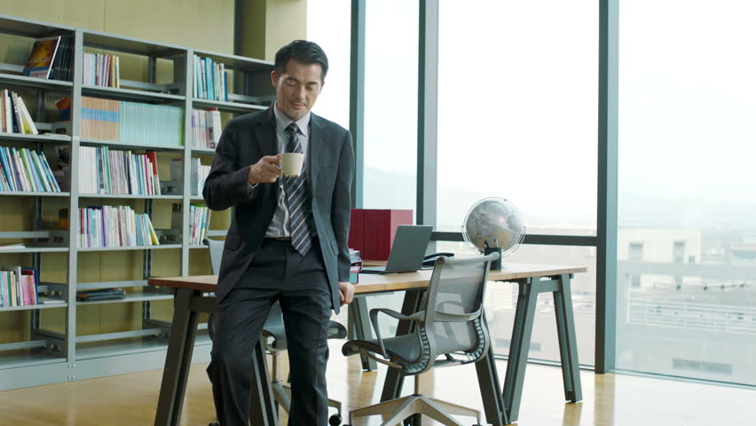 Asian corporate executive drinking coffee while thinking in office