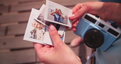 Young daughter on summer vacations with polaroid camera holding vinntage style instant photos with mother