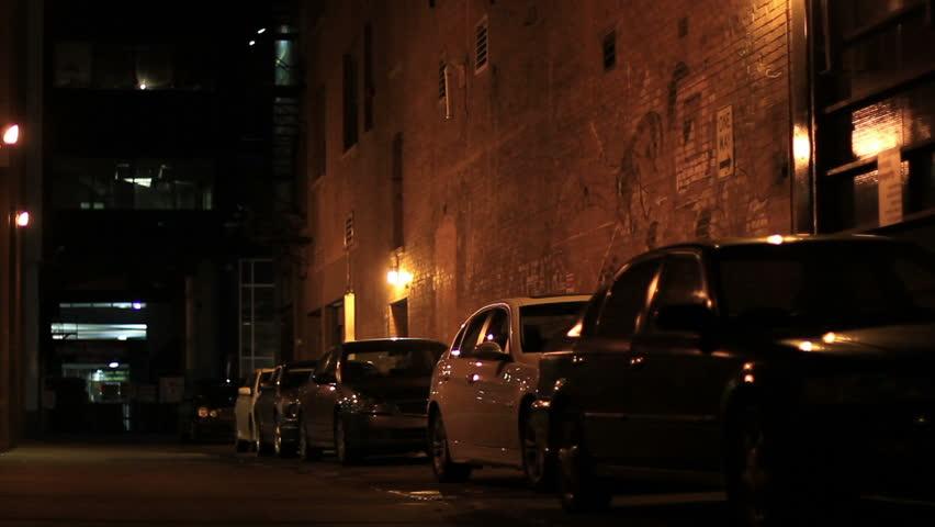 A suspicious man in a hooded sweatshirt walks away down a dark alley downtown