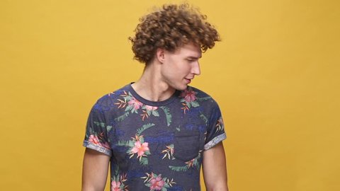 Young crazy guy with curly hair shaking head and screaming while standing isolated over yellow background