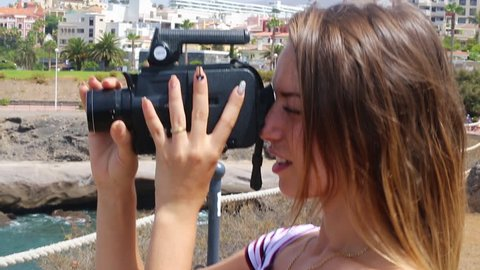 Tenerife. Spain.  Beautiful blond girl on vacation observes and films Playa de Las Americas with vintage camera. With Casa del Duque view. Las Americas is the one of the most popular holiday resort.