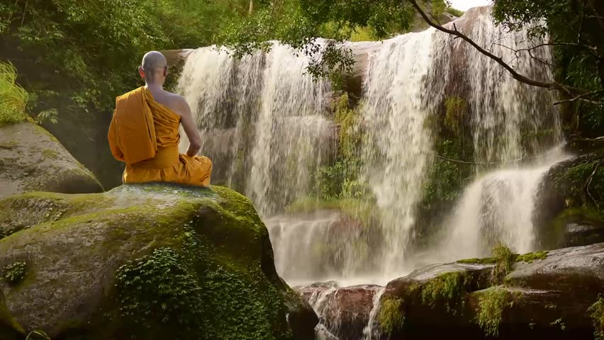 Buddhist monk in meditation at water fall on the mountain.
