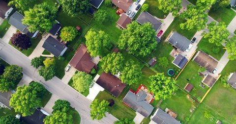 Beautiful neighborhood in summer, at sunrise, moving aerial view.