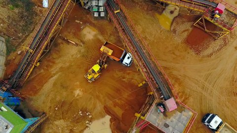 Excavator loader loading sand into dumper truck. Aerial view of excavator loader working on sandpit. Backhoe excavator loading sand in dumper truck