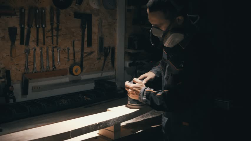 Joiner works with an electric jigsaw, worker make a part of furniture, low light