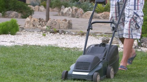 Homeowner working in garden uses lawnmower to mow a lawn. Man in shorts and sandals cutting grass in his yard with corded electric lawn mower.