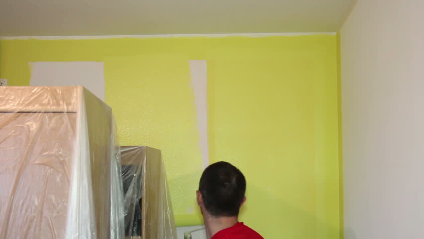 Man Painting A Room Decorator Using Long Roller To Paint Wall In Yellow Hd1080p