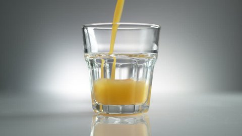 Slow motion shot of Orange juice poured into a glass