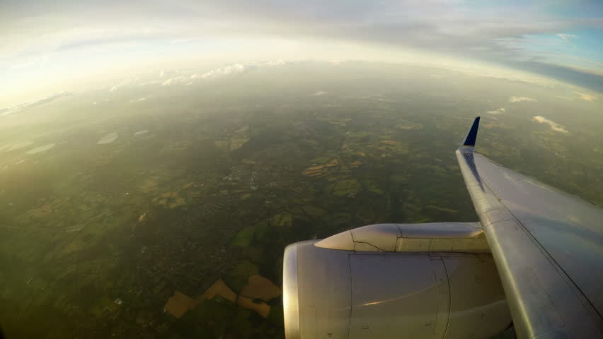 View from aircraft window of engine and England below in holding pattern for Heathrow #29713897