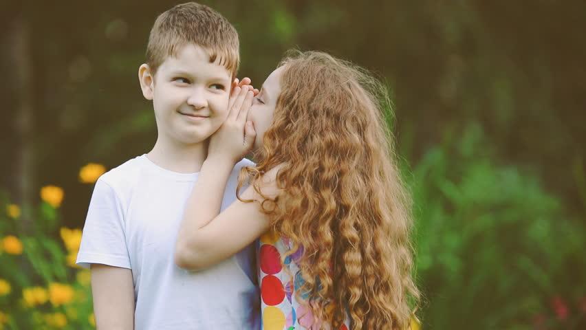Little friends whispering in summer park.