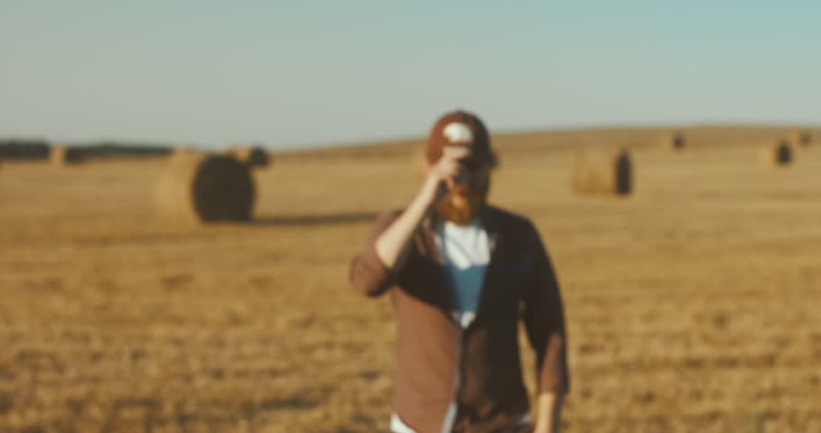 Selective focus, portrait of a farmer walking towards, looking and smiling into the camera, field background. 4K UHD 60 FPS