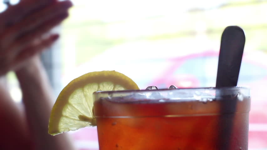 Lemon sitting ontop of glass of Iced Tea in restaurant