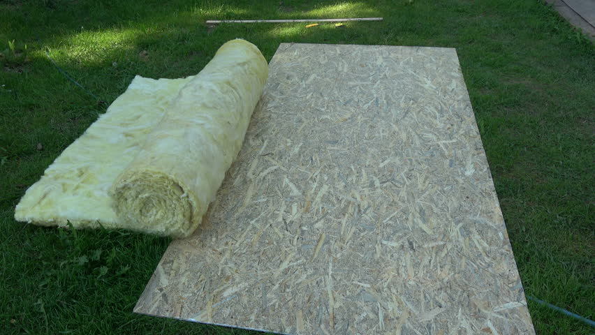 Worker in farm yard rolling new house insulation material rock wool