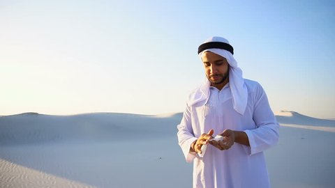 Sad handsome young man, sheikh ill with cold and feels unwell, eases breathing with handkerchief and looks to side, standing in middle of bottomless desert with snow-white sand on sunny summer day